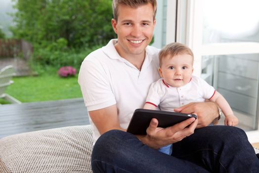Portrait of a father and son with a digital tablet in a home interior