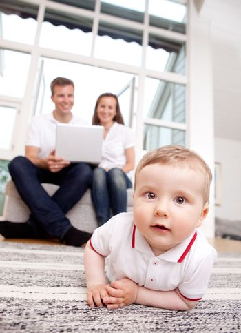 A happy curious young baby boy with parents in the background using computer
