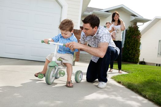 Father teaching his son to ride tricycle while wife standing in background