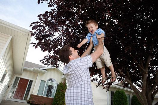 Happy father lifting his cute son in the air