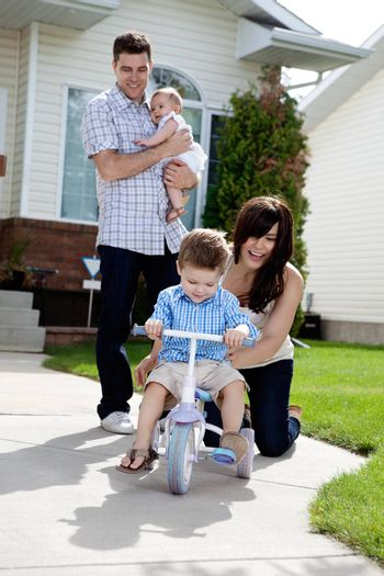 Cheerful mother teaching son to ride tricycle while husband holds daughter in background