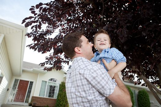 Father Lifting His Little Adorable Boy In Front Of House.