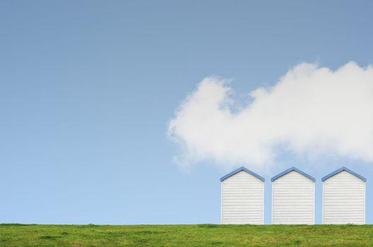 Three Beach Huts on Blue Sky
