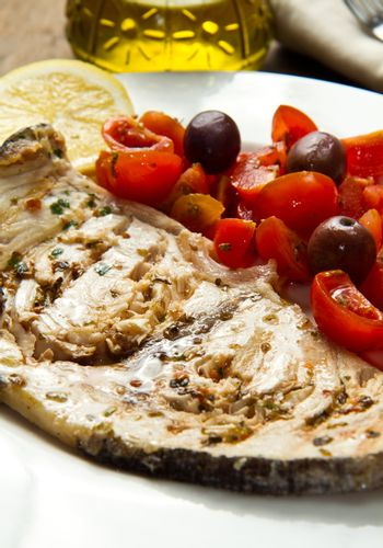 swordfish with tomatoes and lemon on wood