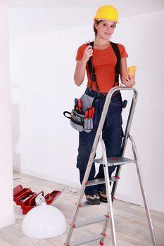 Female installing lamp