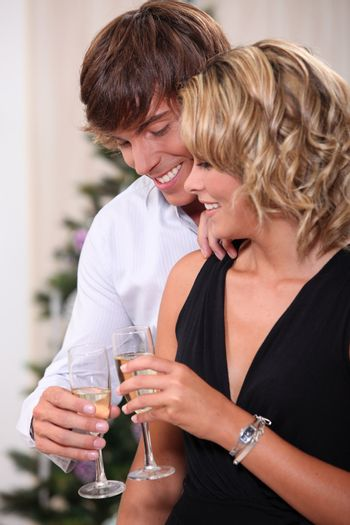 Couple drinking champagne in front of a Christmas tree