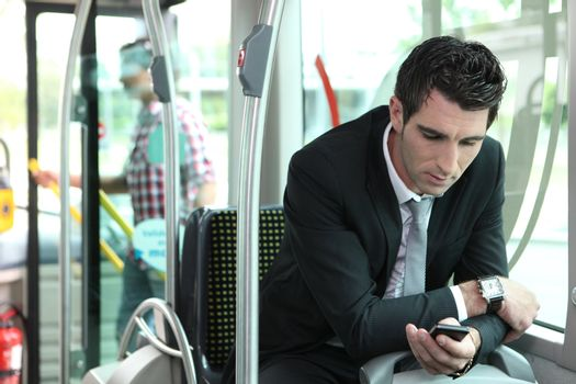 man texting in a bus