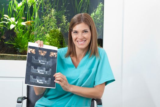 Portrait of a happy female dentist holding dental X-ray in clinic