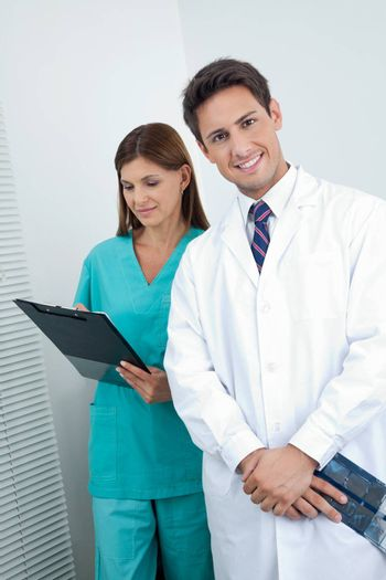 Portrait of happy male dentist with assistant holding clipboard in clinic