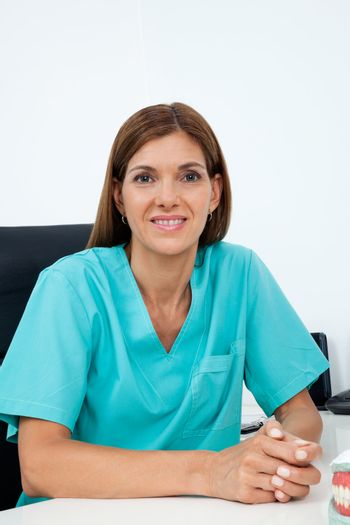 Portrait of mid adult female dentist smiling at desk