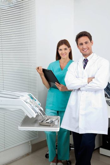 Portrait of young male dentist and assistant standing in dental clinic