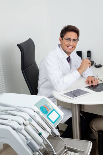 Portrait of a happy young male dentist sitting at office desk