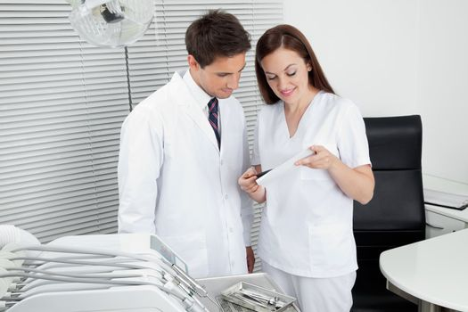 Male dentist with assistant discussing dental report in clinic