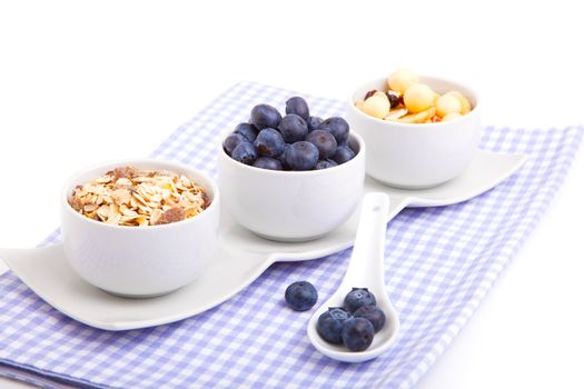fresh blueberry with porcelain spoon, corn flakes and serviette.