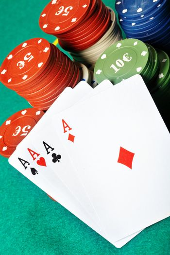 Set of four aces and poker chips on a green table