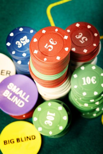 Stack of poker chips on a green table of casino