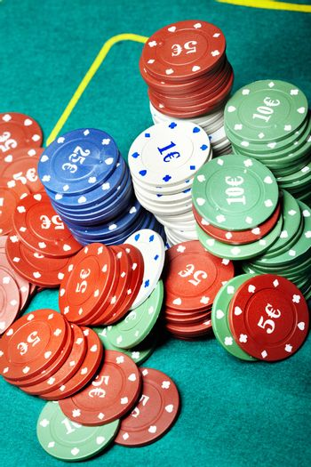 Vertical close-up photo of the various casino chips on a green table