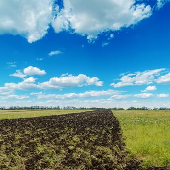 blue cloudy sky and plouwed field
