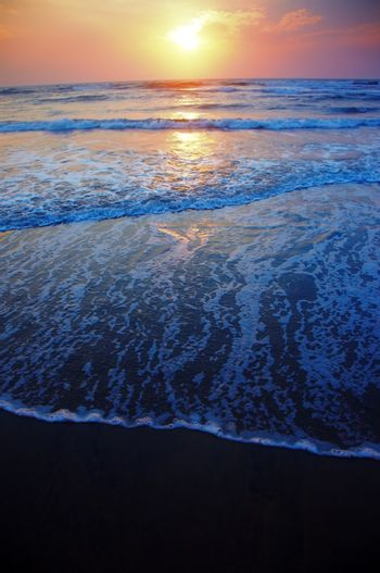 Vertical photo of the sea during sunset. Natural darkness and colors