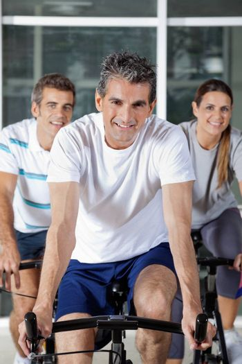 Portrait of three happy people on exercise bikes in health club