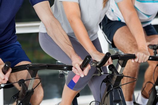 Mid section of men and woman on exercise bikes in health club
