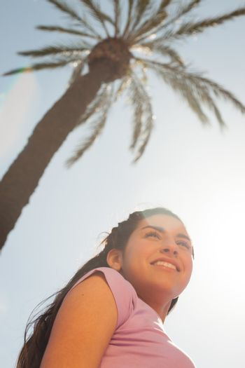 Young beautiful woman portrait with sun flare from above