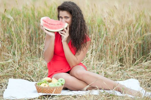 Woman in wheat field eating watermelon. Picnic.
