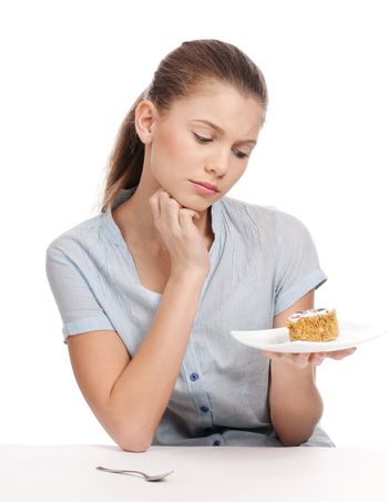 Pretty young woman eating cake. Isolated