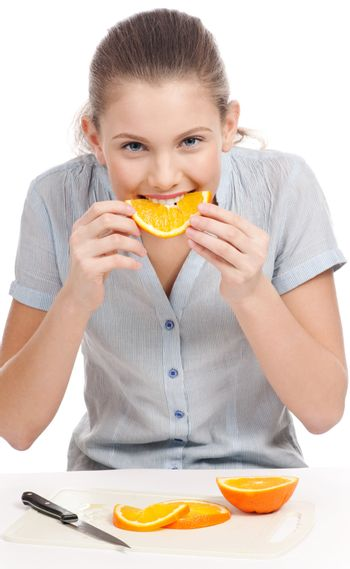 Pretty young woman eating orange. Isolated
