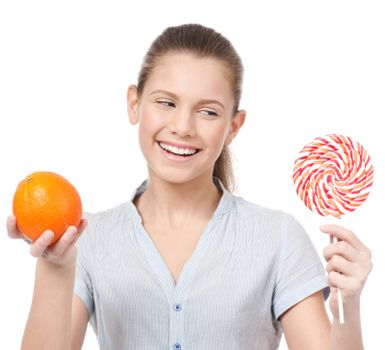 Pretty young woman with lollipop and orange. Choice