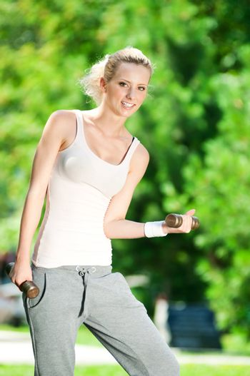 Woman doing dumbbell exercise outdoor