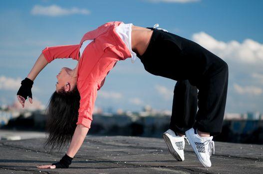 woman dancing hip hop over blue sky