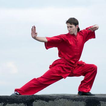 Shaolin warriors wushoo man in red practice martial art outdoor. Kung fu