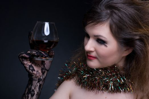 Closeup portrait of girl with red lips, tinsel and wineglass on