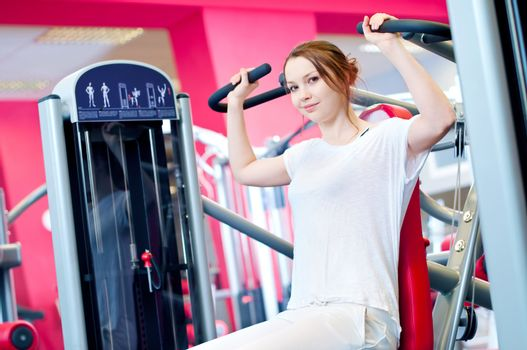 Woman doing splits on machine with weights