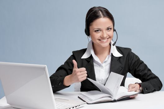 Busy business woman in office place talking by wireless headset over white table, laptop and diary. Thumbs up!