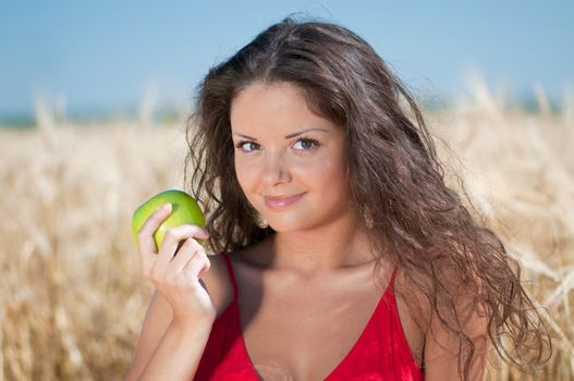 Perfect woman eating apple in dield. Summer picnic.