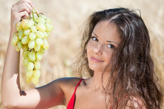 Nice woman in wheat field eating grapes.