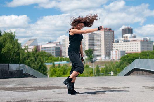 Beautiful girl dancing hip-hop over urban landscape
