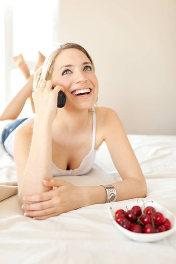 beautiful white women having a happy conversation looking up on bed with cherries bowl