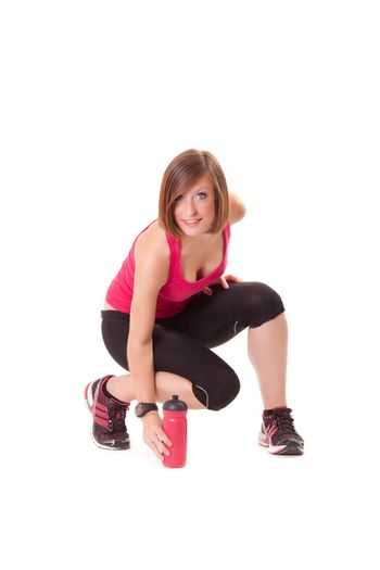young beautiful sport woman takes a bottle and smile isolated on white background
