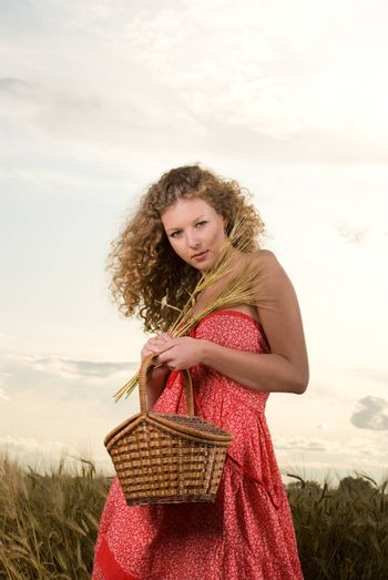 Beautiful slavonic girl pose in wheat field with basket