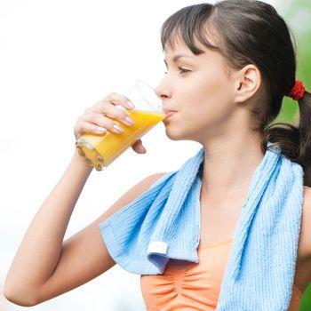 Teenage girl drinking orange juice after fitness exercise