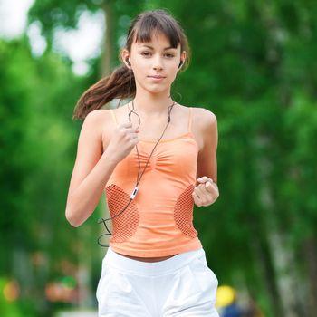 Beautiful teenage girl running in green park on sunny summer day