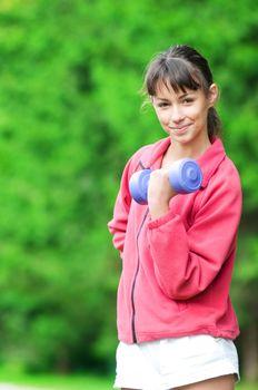 Girl doing dumbbell exercise outdoor