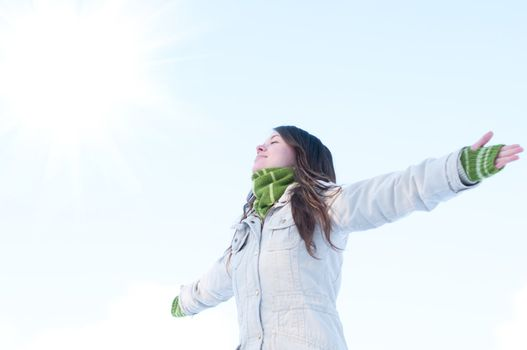 Winter lifestyle. Beautiful girl with green scarf and gloves over blue sky and sun