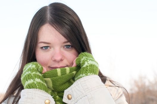 Beautiful girl in green over winter landscape