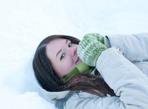 Beautiful girl in green lying in snow