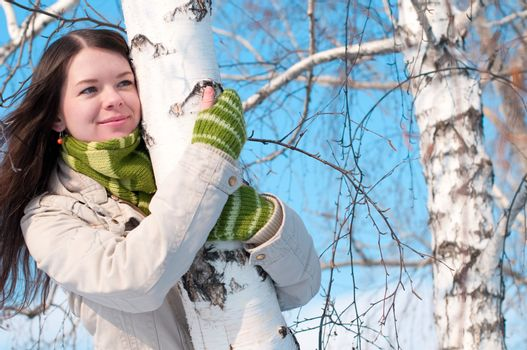 Beautiful girl in green over tree and blue sky