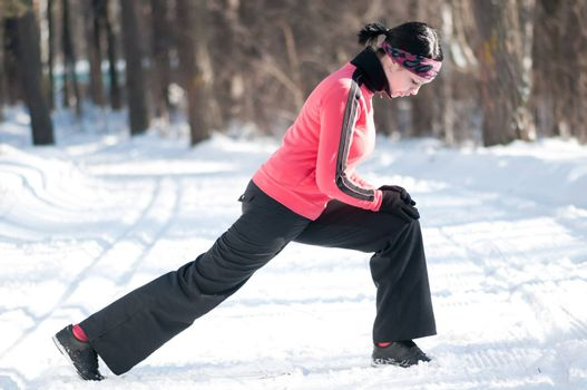 Beautiful young sport woman doing stretching fitness exercise in winter forest